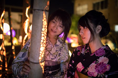 Mother and daughter in yukata looking at bamboo candle lights
