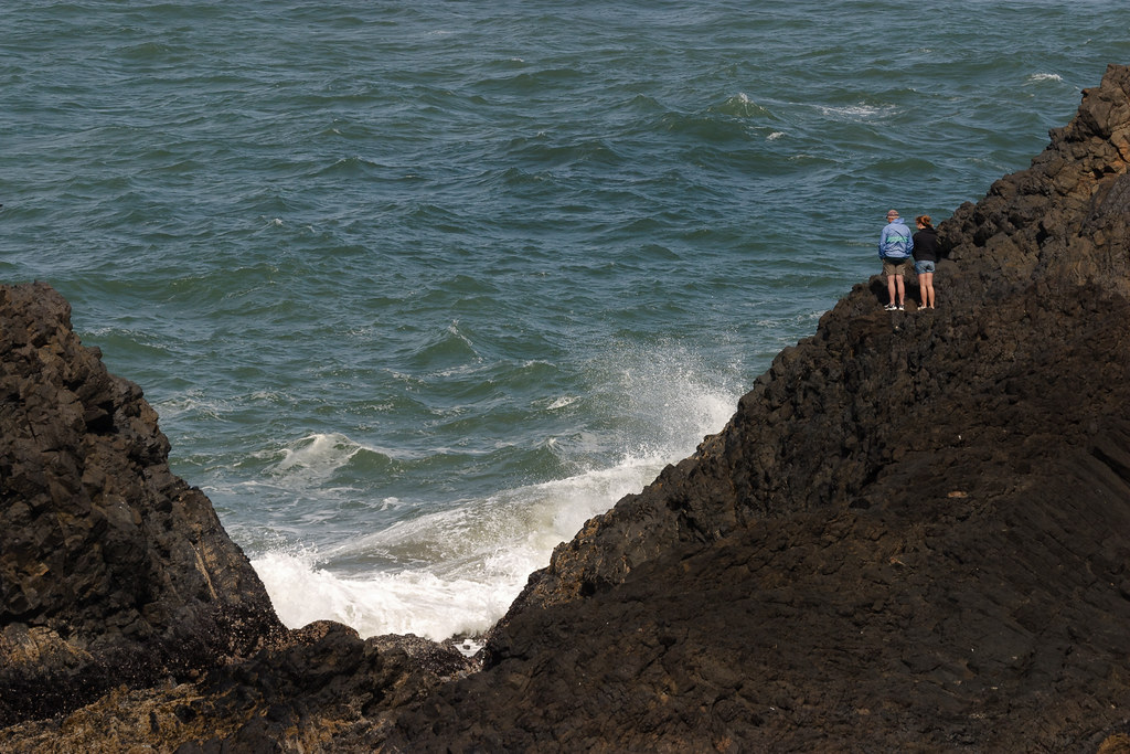 Two people watch the endless crashing of waves against the rocky shore of Seal Rock State Park on the Oregon coast