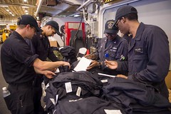 Sailors assigned to the USS America (LHA 6) supply department inventory coveralls in the ship's hangar bay, Aug. 21. (U.S. Navy/MC2 Kristina Young)