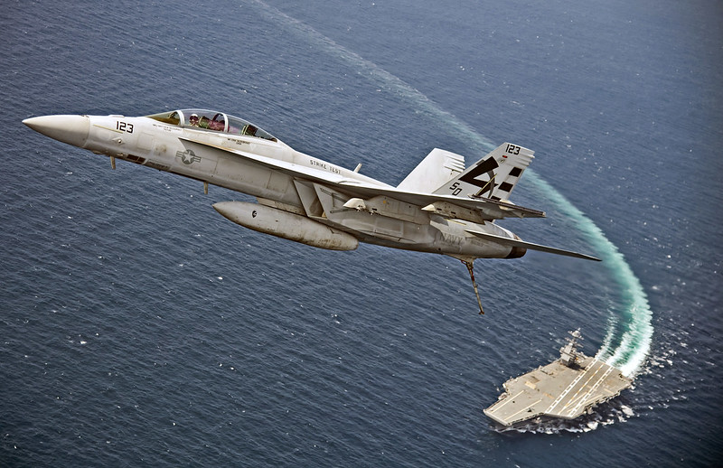 An F/A-18F Super Hornet flies over USS Gerald R. Ford.