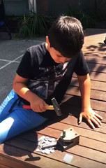 Child striking ancient coin replica