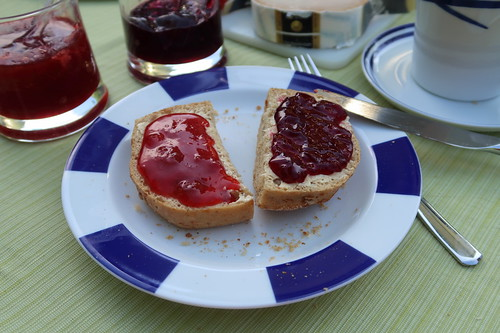 Erdbeermarmelade und Brombeergelee auf weißem Brötchen