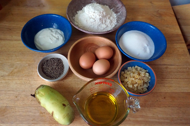 Baking ingredients, each in their individual bowls, laid out in a circle surrounding the central wooden bowl holding three brown eggs. It feels like a baking mandala.