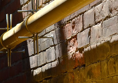 yellow pipes on old brick wall