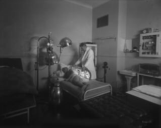 Château Laurier Hotel - man receives carbon heat ray treatment in the electric treatment room... / Hôtel Château Laurier - un homme reçoit un traitement aux rayons de chaleur au carbone dans la salle de traitement électrique...