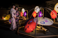 Portrait of mother and daughter in yukata, standinging in paper umbrella lights