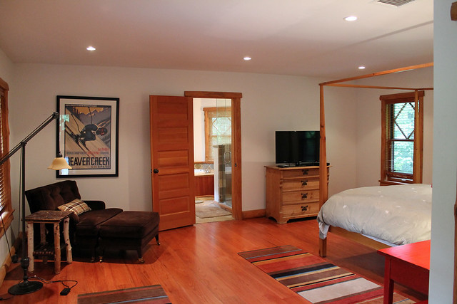 Queen bedroom with hardwood floors and sitting area; full private bath