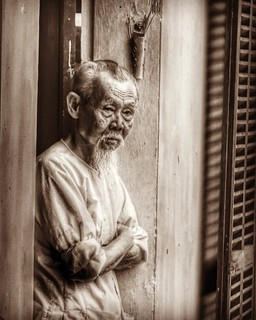 A Vietnamese wood carver watches the tourists from his shop doorway. Hoi An, Vietnam.