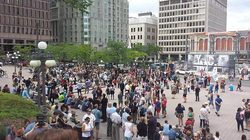 La grande Place d'Youville est à moitié couverte de gens. Les gens discutent avant le départ.