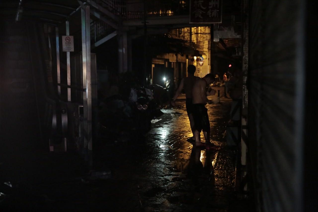 澳門風災的重災區停水停電,有市民走到街上使用街喉洗澡。(林若勤攝)