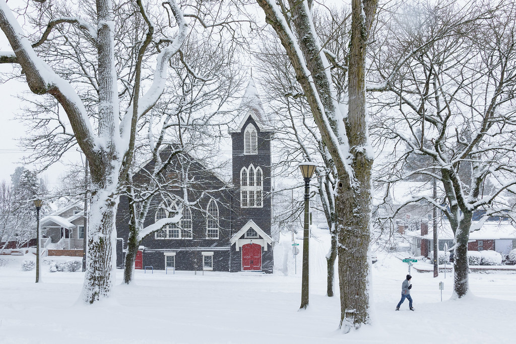 A lone pedestrian walks through a snowy Irving Park with the Door of Hope church in the background
