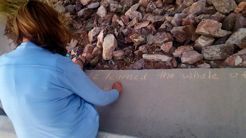 Cynthia Holmes chalking We Learned the Whole of Love  by Emily Dickinson in the Malvern Plaza {Urban Poetry Pollinators)
