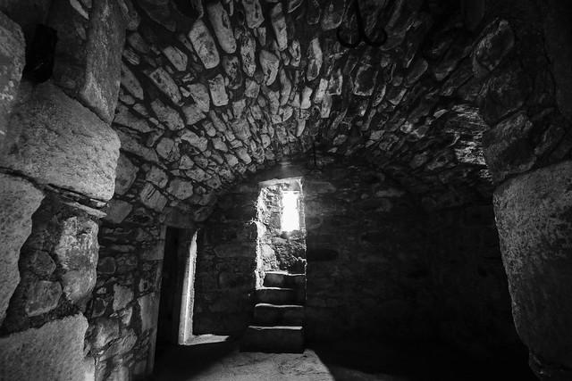 dark stone vault presses down on stairs into the bright light, inside Tolquhon Castle, Aberdeenshire, Scotland - fine art black & white