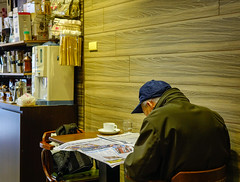Old man reading news at the coffee shop