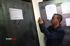 "People inspect the closure notices, which state that companies are closed for 6 months, are hang by Israeli soldiers after they conduct a raid to ""Palmedia"" and ""TransMedia"" companies in Ramallah"