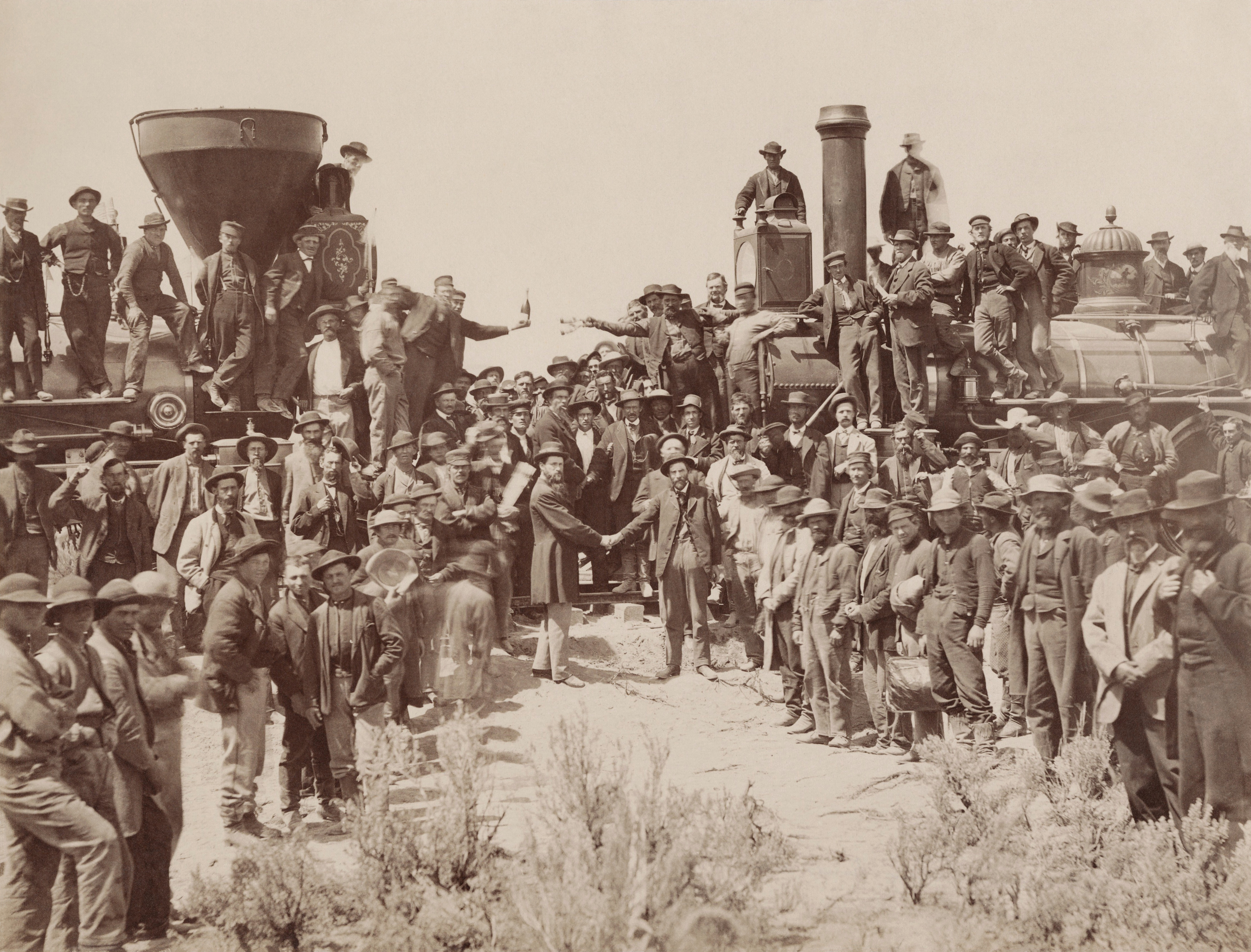 The ceremony for the driving of the golden spike at Promontory Summit, Utah on May 10, 1869; completion of the First Transcontinental Railroad. At center left, Samuel S. Montague, Central Pacific Railroad, shakes hands with Grenville M. Dodge, Union Pacific Railroad (center right).