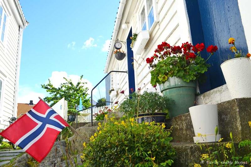 Puerta de entrada a una de las casas del barrio de Gamle, con la bandera nacional noruega a los pies
