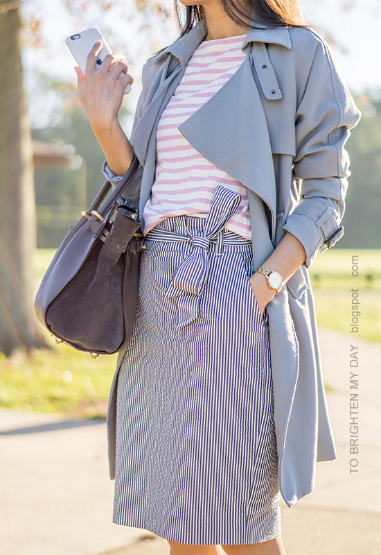 gray draped trench coat, pink striped top, gold watch, striped seersucker pencil skirt with bow, gray tote