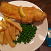 Fish and chips, peas, tartare sauce and vinegar.