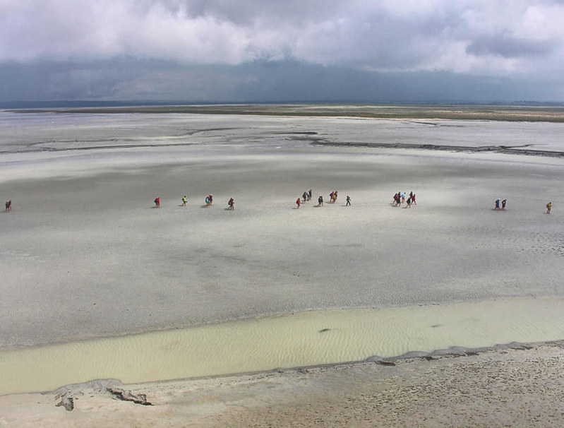 People walking along the clay sands of the bay around Mont-Saint-Michel. Credit tiger rus