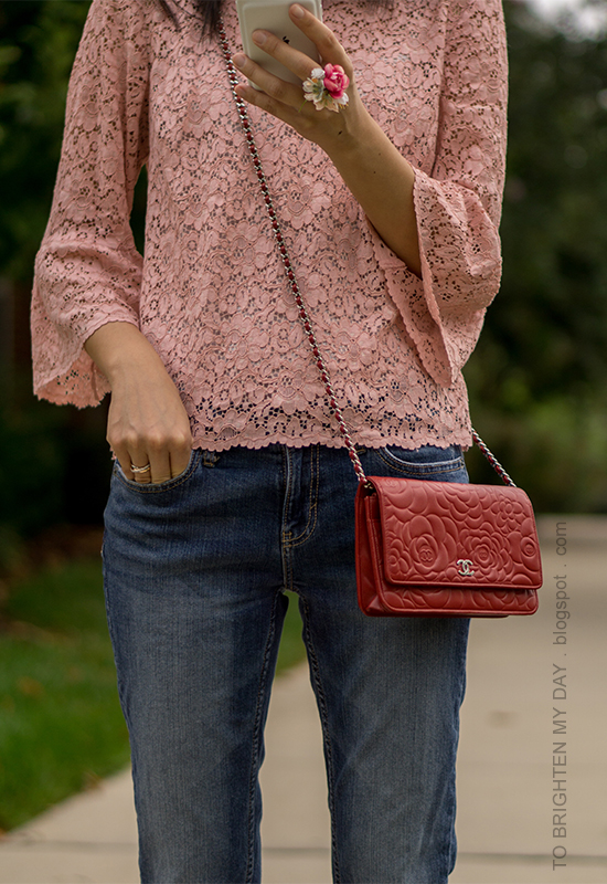 pink lace top with bell sleeves, floral ring, red embossed crossbody bag, girlfriend jeans