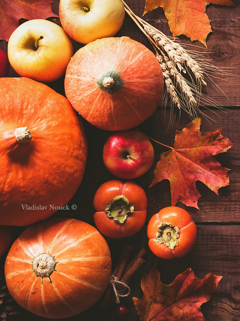 Thanksgiving background with pumpkins, apples and fallen leaves on wooden table
