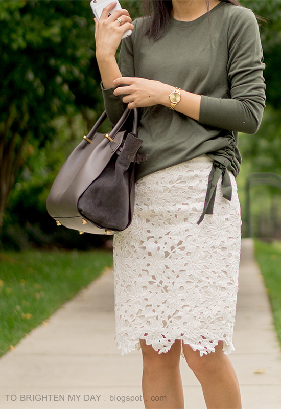 green top with side ties, gold watch, infinity rings, gray suede tote, beige floral pencil skirt