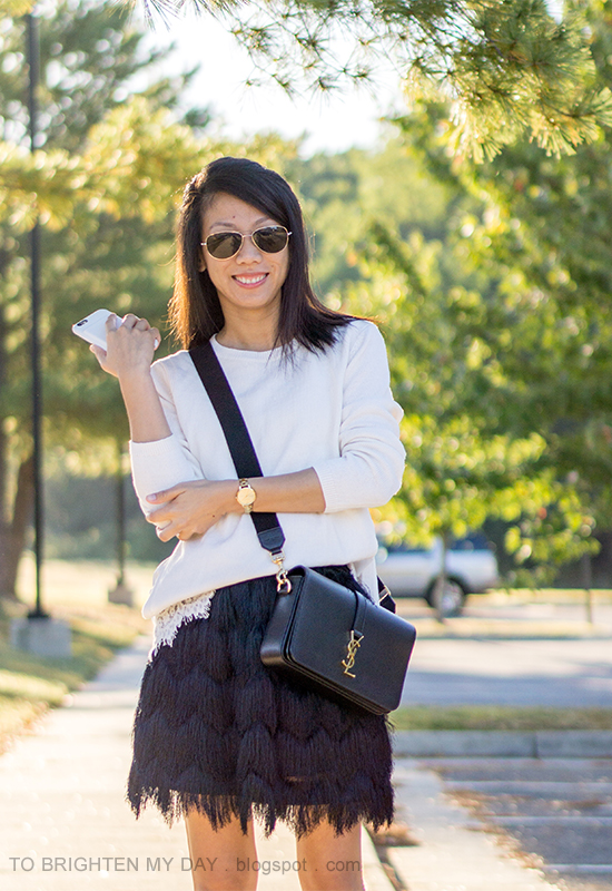 white sweater with lace hem, gold watch, black crossbody bag, black fringe skirt