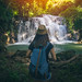 Young woman traveler travel into amazing beautiful waterfalls in tropical forest