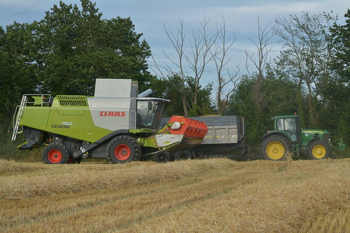 Claas Lexion 750 Combine Harvester unloading Winter Barley to a Beresford Trailer drawn by a John Deere 7530 Tractor