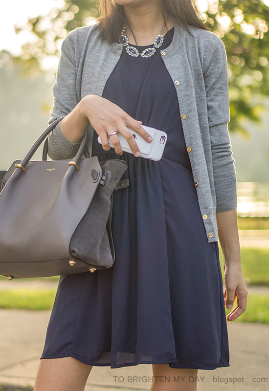 blue gemstone necklace, gray cardigan, navy pleated dress, gray tote bag