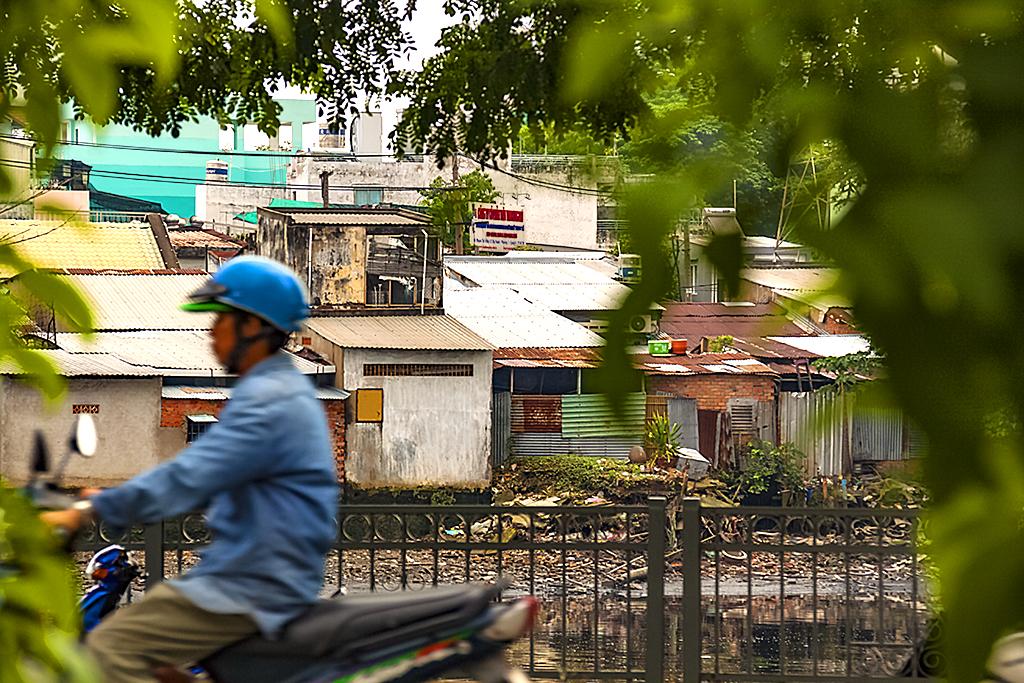 Shabby houses by canal--Saigon