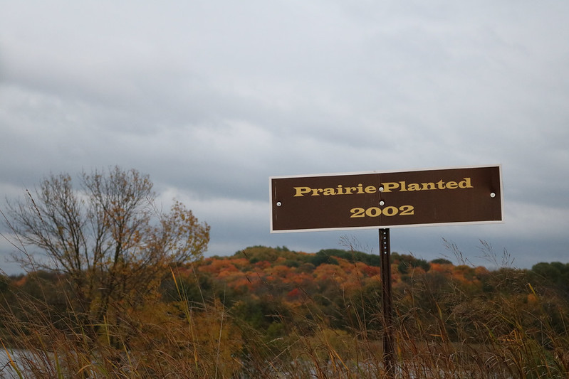 dark brown sign: Prairie Planted 2002, with colorful trees in the background