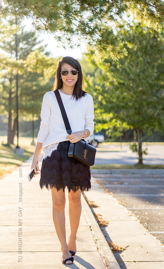 white sweater with lace hem, gold watch, black crossbody bag, black fringe skirt, bow ballerina flats