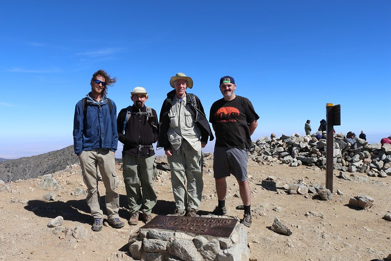 The four of us posing with the brass plaque on the summit of Mount Baldy