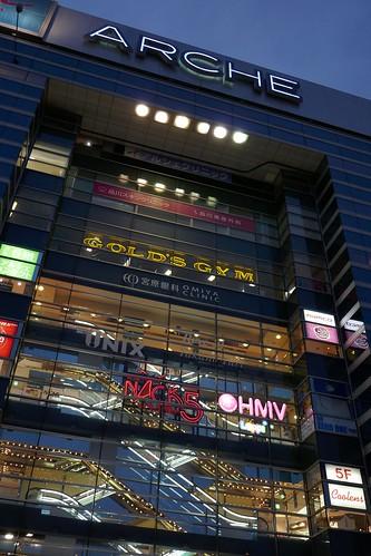 """Omiya_(2017_10_18)_3_resized_1 埼玉県さいたま市大宮駅前の """"ARCHE"""" の高層ビルディングの写真。 日没時で薄暗い。 各階の上下のエスカレーターが交差し、明るく輝いている。 ガラス張りの壁面には多数の入居店舗のロゴが描かれ輝いている。"""