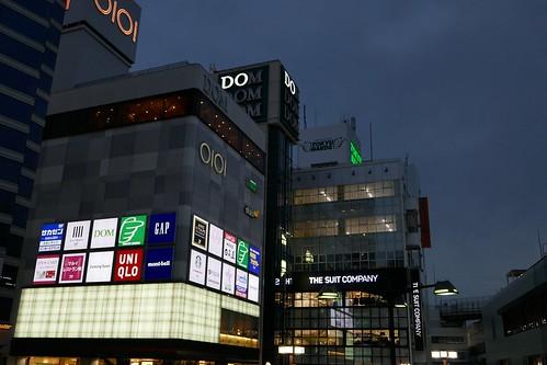 Omiya_(2017_10_18)_2_resized_1 埼玉県さいたま市大宮駅近辺の都市の風景写真。 薄暗い日没時の高層ビルディングが写っている。 商業ビルディングの壁面には入居店舗の光り輝く看板が多数並んでいる。