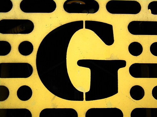 The letter 'G' cut out of yellow metal