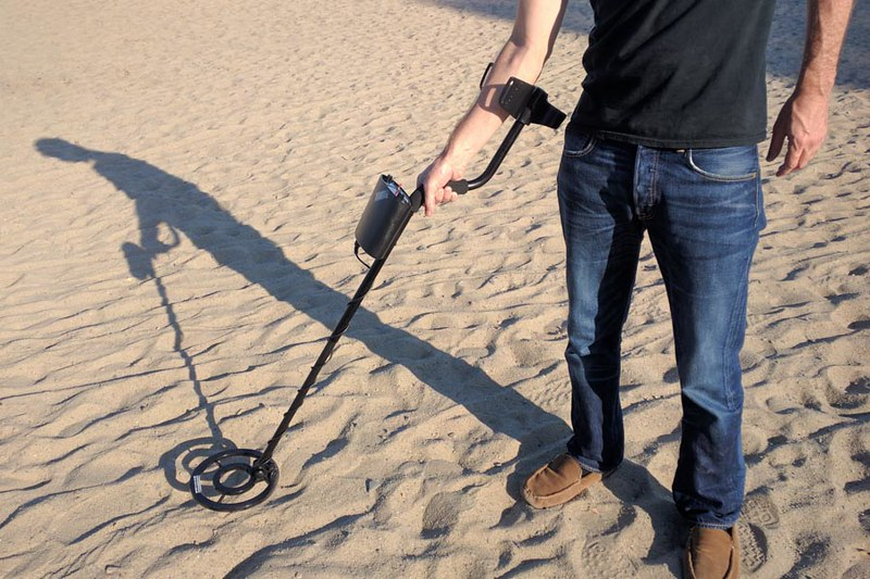 man holding metal detector on sand
