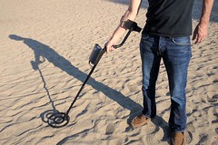 man holding metal detector on sand