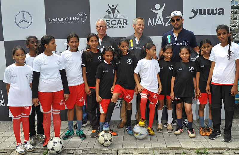 (L-R)-Roland-Folger,-Andy-Griffiths-and-newly-appointed-brand-ambassador-Yuvraj-Singh-with-girls-under-the-Laureus-Sport-for-Good-programme
