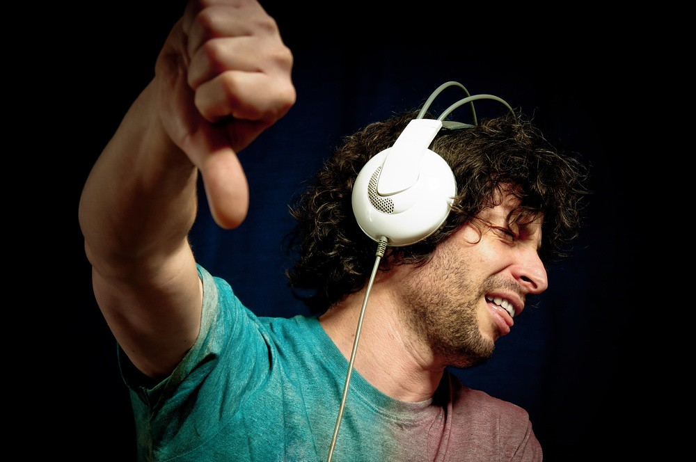 music listener with headphones giving thumbs-down gesture