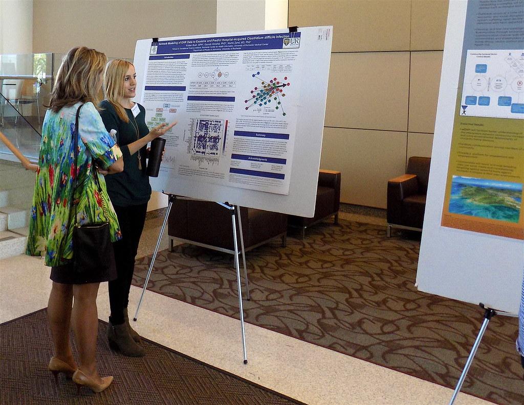Kristen Bush explains poster to attendee