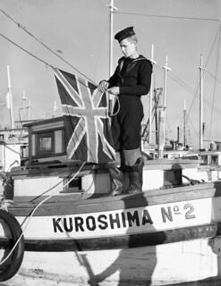 A Canadian sailor prepares to hoist the Union Jack flag on the confiscated Japanese-Canadian fishing boat, KUROSHIMA No. 2, New Westminster, British Columbia / Un matelot canadien installe le drapeau de l'Union royale (Union Jack) sur le bateau de pê