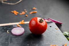 A tomato and other vegetables in the kitchen , dark background