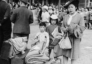 Japanese-Canadian woman, girl and boy wait to be relocated to a camp in the interior of British Columbia / Garçon, fille et femme déplacés à un camp de la région intérieure de la Colombie-Britanniqu