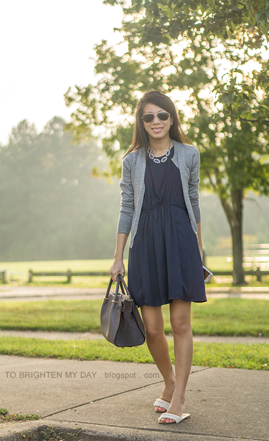 blue gemstone necklace, gray cardigan, navy pleated dress, gray tote bag, white flats with embellishments