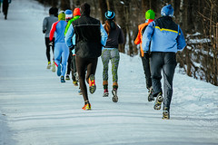 group of athletes running on winter alley
