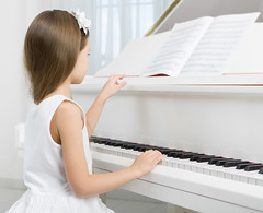 Side view of little girl in white dress playing piano. Concept of music study and art
