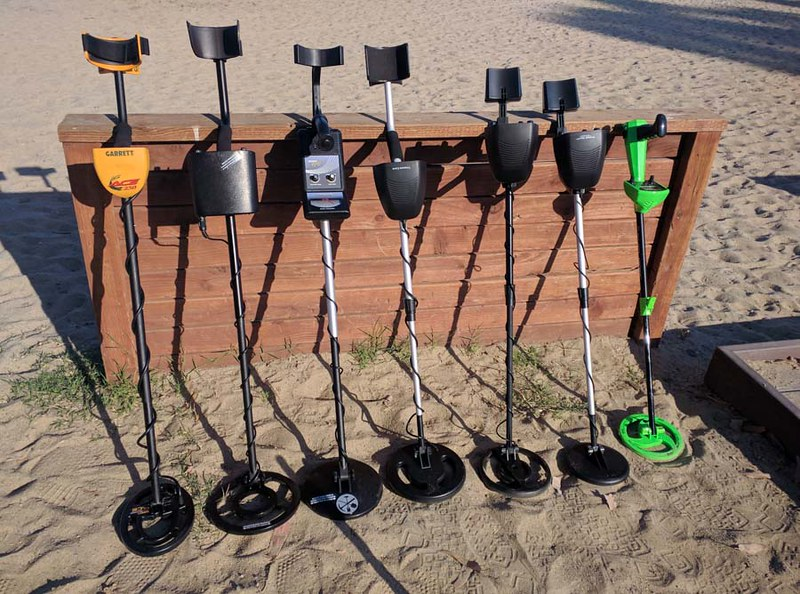 metal detectors resting on a wall at the beach